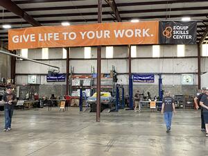 """A photo of the Equip Skills Center garage. A few people are at work in the garage under a banner that reads """"Give life to your work."""""""